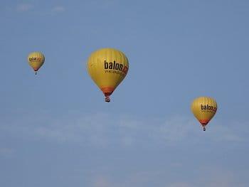 Tři žluté balóny na cestě
